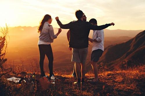 sortie : groupe de trois personnes sur une coline face à une montagne.