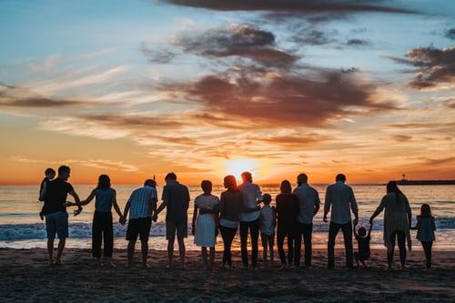 sortie au centre social et culturel : groupe de plusieurs personnes à la plage en bord de mer devant un couché de soleil.